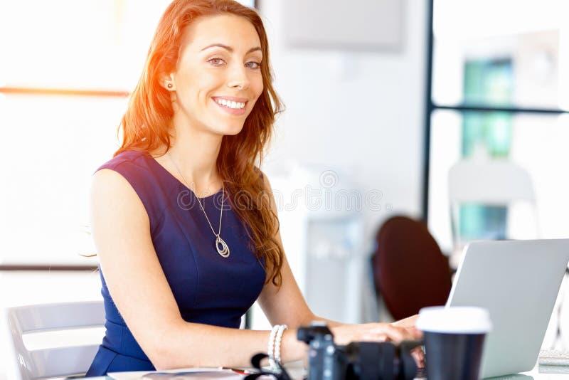 Porträt der Geschäftsfrau arbeitend an ihrem Schreibtisch im Büro lizenzfreie stockfotos