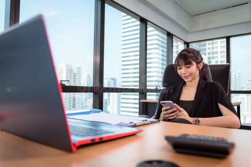 Porträt der Geschäftsfrau benutzt Handy an Büro-Arbeitsplatz, attraktive schöne Geschäftsfrau plaudert Mitteilung an lizenzfreies stockfoto