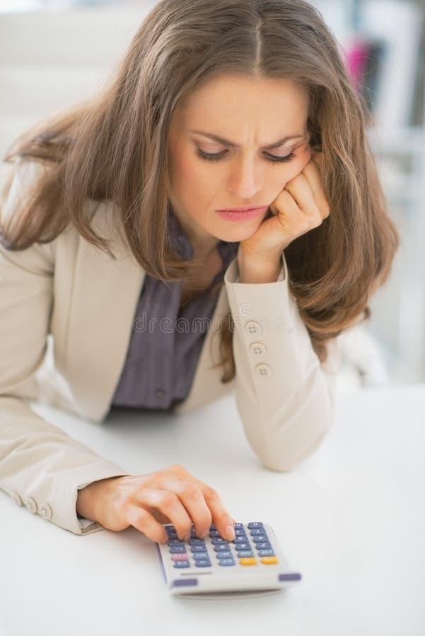 Porträt der Geschäftsfrau, die Taschenrechner verwendet lizenzfreies stockbild