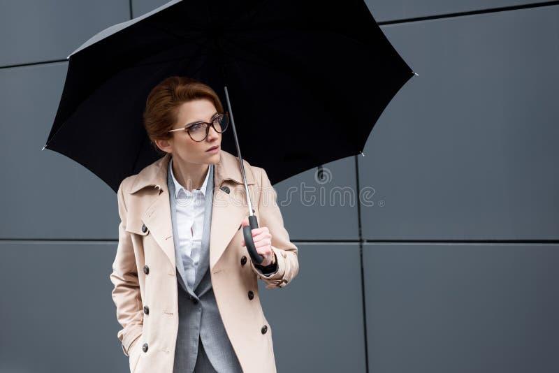 Porträt der Geschäftsfrau im modischen Mantel mit Regenschirm stockfotos