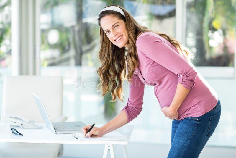 Porträt der Geschäftsfrauschreibensanmerkung lizenzfreies stockbild
