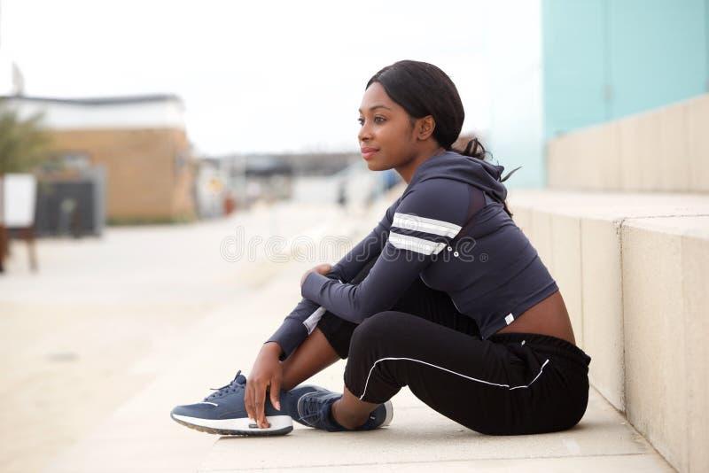 Porträt der gesunden jungen Sportfrau, die draußen auf Boden sitzt stockfoto