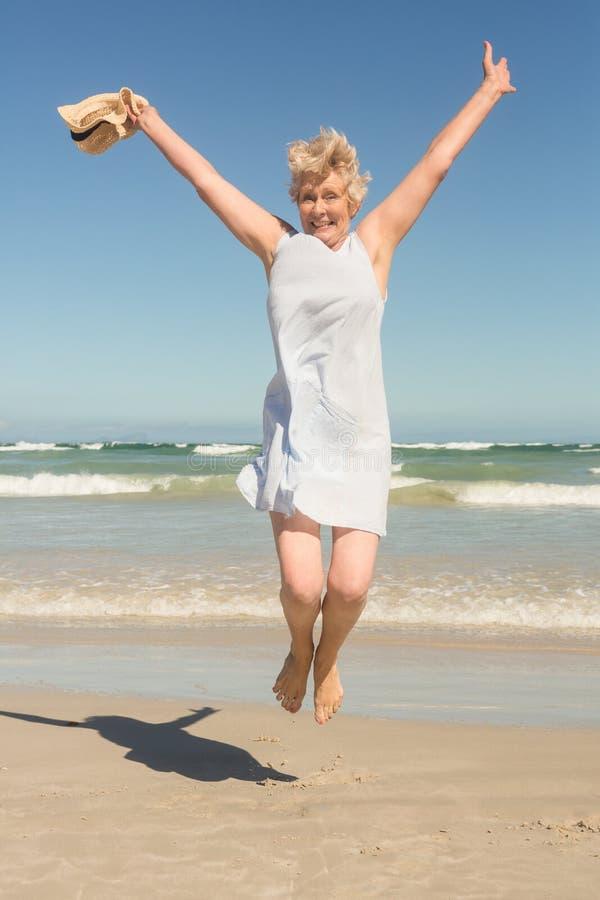 Porträt der glücklichen älteren Frau, die auf Sand gegen klaren Himmel springt lizenzfreies stockfoto