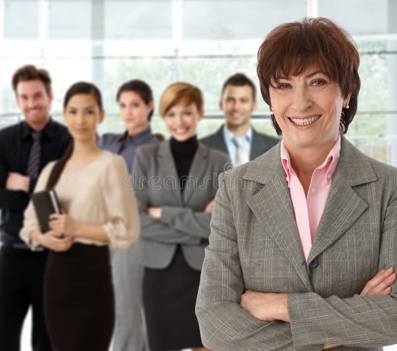 Porträt der glücklichen älteren Geschäftsfrau und des Teams lizenzfreies stockbild