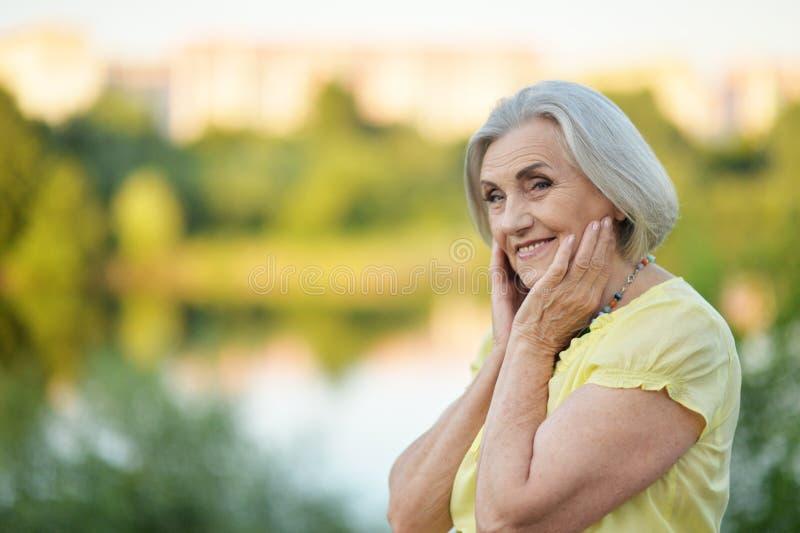 Porträt der glücklichen älteren Schönheit durch See lizenzfreies stockbild