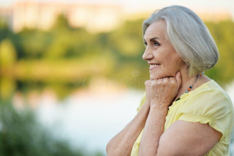 Porträt der glücklichen älteren Schönheit durch See lizenzfreies stockfoto