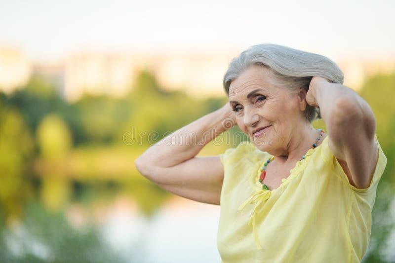 Porträt der glücklichen älteren Schönheit durch See stockfotografie