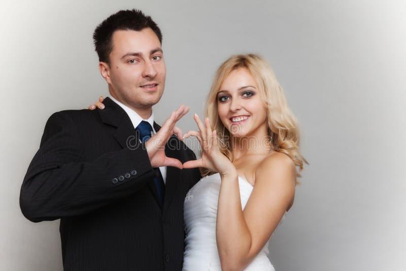 Porträt der glücklichen Braut und des Bräutigams, die Herz zeigt, unterzeichnen stockfotos