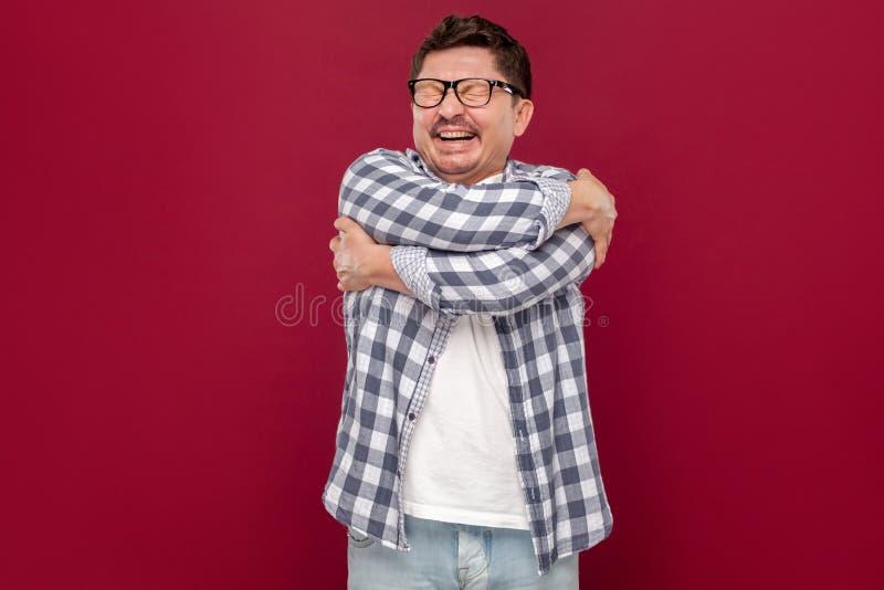 Porträt der glücklichen erfüllten hübschen Mitte alterte Geschäftsmann im zufälligen karierten Hemd, die Brillenstellung und umar lizenzfreie stockfotografie