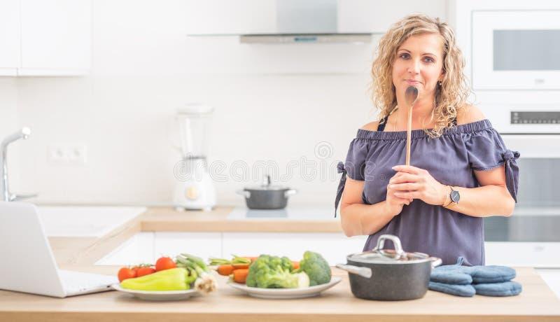 Porträt der glücklichen erwachsenen Frau in ihrer modernen Küche mit Topf und Gemüse lizenzfreie stockbilder