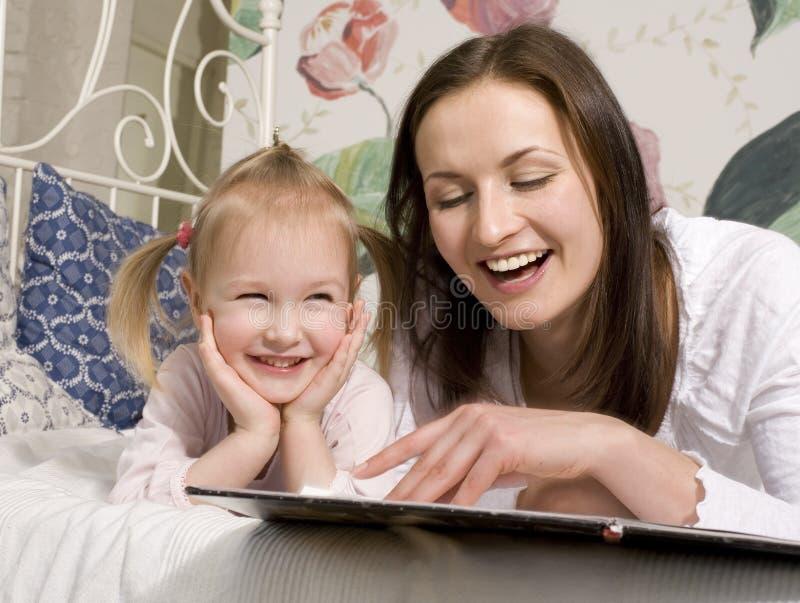 Porträt der glücklichen Familie, der Mutter und der Tochter im Bett stockfoto