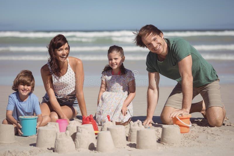 Porträt der glücklichen Familie Sandburg am Strand machend lizenzfreie stockfotos
