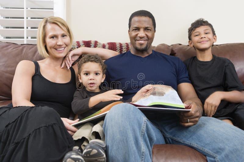 Porträt der glücklichen Familie sitzend auf Sofa stockfotos
