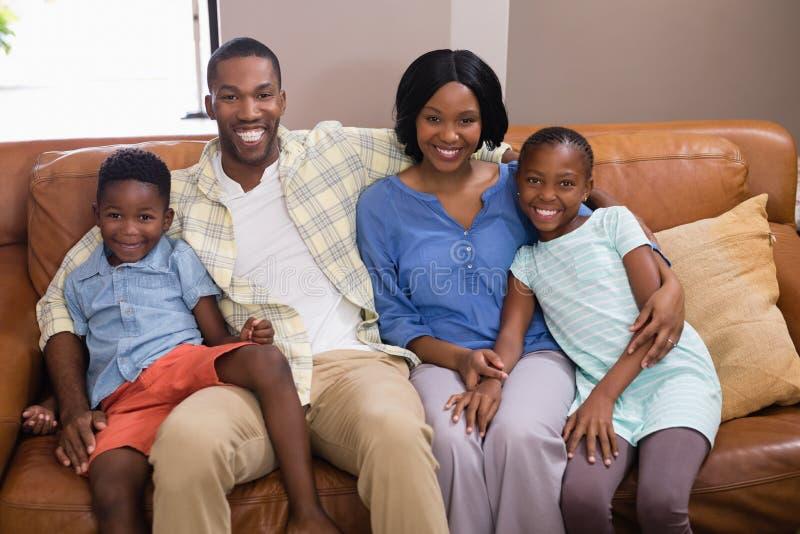 Porträt der glücklichen Familie sitzend auf Sofa stockfotografie