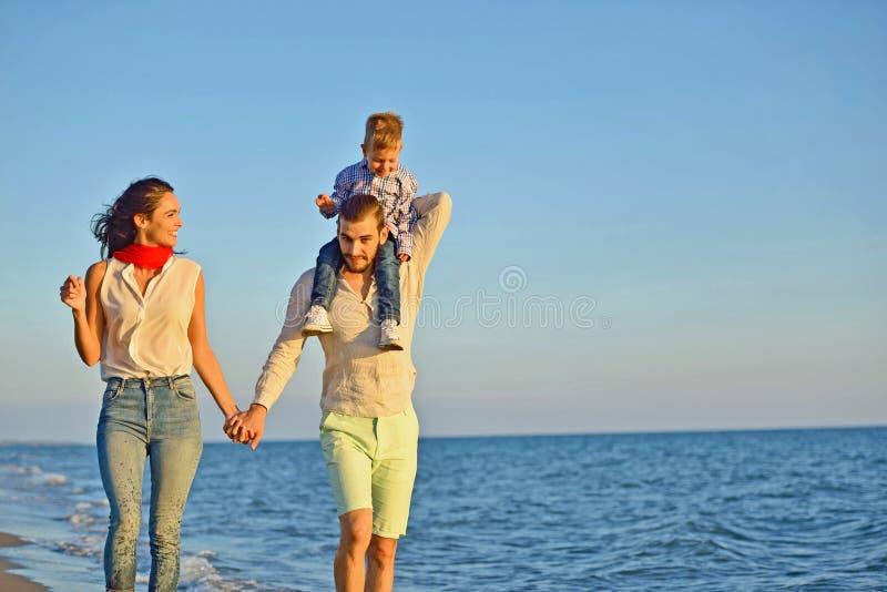 Porträt der glücklichen Familie und des Babys, die Sonnenuntergang in der Sommerfreizeit genießt stockbild
