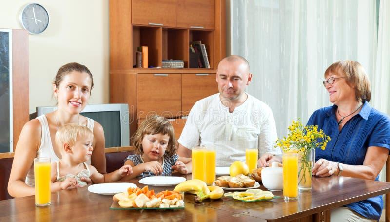 Porträt der glücklichen Familie von mehreren Generationen, die friuts mit jui isst stockfotografie