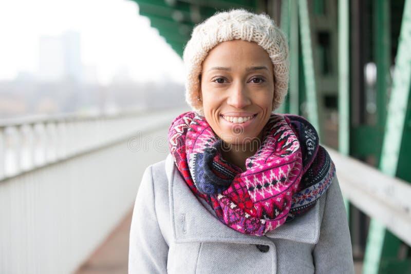 Porträt der glücklichen Frau in der warmen Kleidung, die draußen steht stockbild