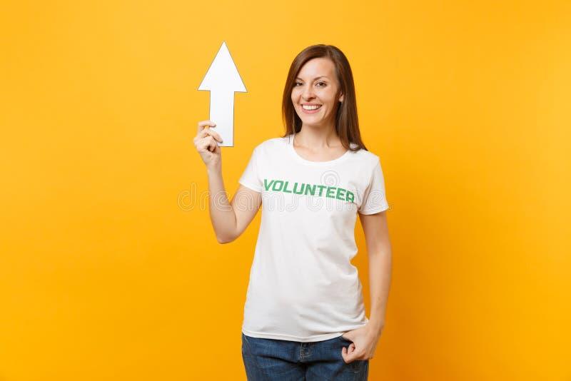 Porträt der glücklichen Frau im weißen T-Shirt mit schriftlichem Aufschriftgrüntitel freiwilliger Griffpfeil zeigend oben lokalis stockbild