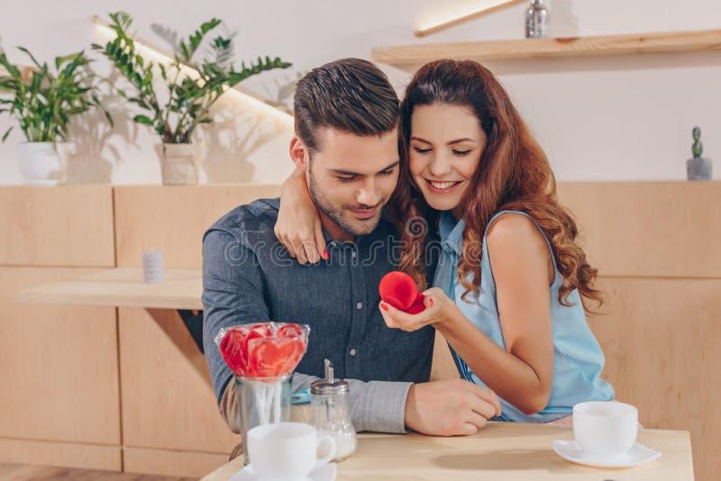 Porträt der glücklichen Frau mit dem Verlobungsring in der Hand, der Freund umarmt lizenzfreies stockbild