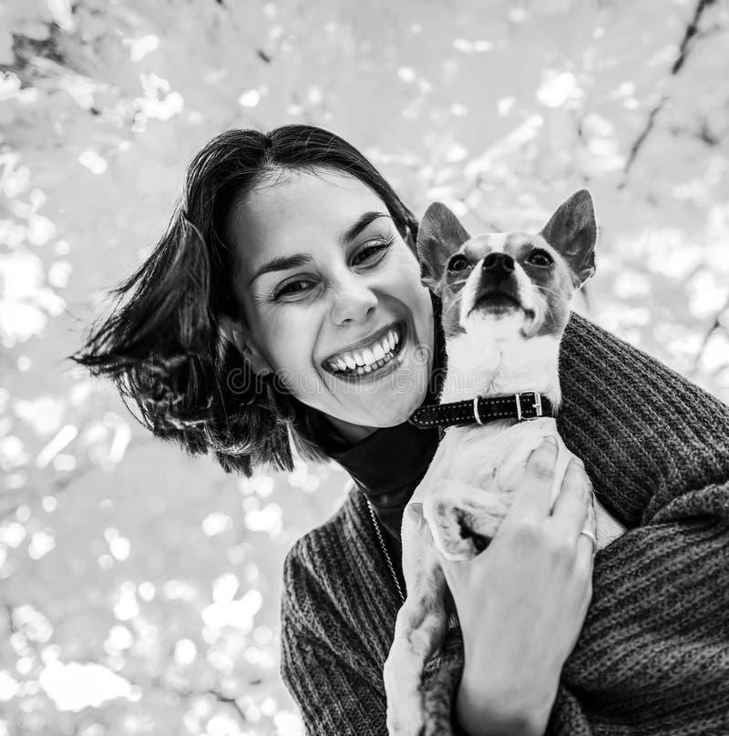 Porträt der glücklichen Frau mit Hund draußen im Herbst lizenzfreie stockbilder