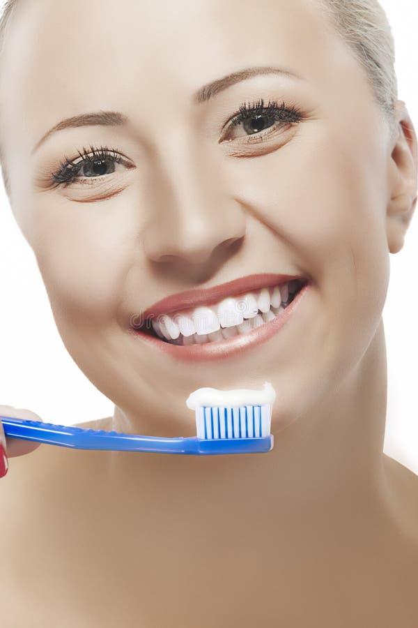 Porträt der glücklichen gebräunten kaukasischen Frau, die manuelles Toothbru hält lizenzfreie stockbilder