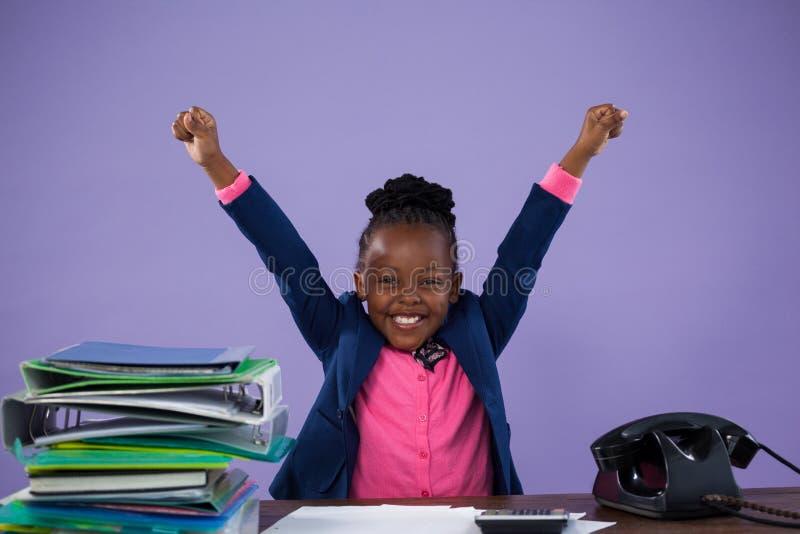 Porträt der glücklichen Geschäftsfrau mit den Armen hob am Schreibtisch an stockbild