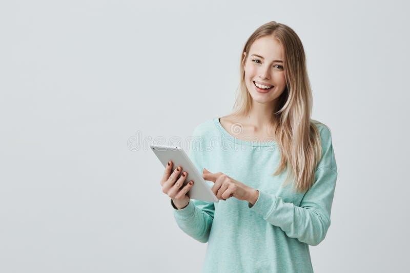 Porträt der glücklichen jungen blonden Geschäftsfrau in der zufälligen Kleidung unter Verwendung der Tablette lokalisiert gegen g lizenzfreie stockbilder