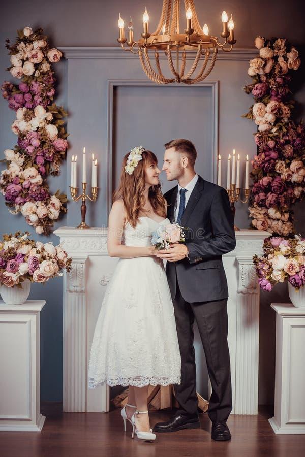 Porträt der glücklichen jungen Braut und des Bräutigams in einem klassischen Innenraum nahe dem Kamin mit Blumen Hochzeitstag, Li stockbild