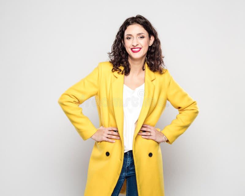 Porträt der glücklichen jungen Frau in der gelben Jacke lizenzfreie stockbilder