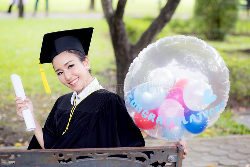 Porträt der glücklichen jungen Frau graduiert in der akademischen Kleider- und Quadrat Academickappe stockfotografie