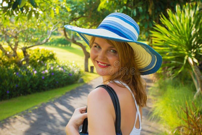 Porträt der glücklichen jungen Frau im tropischen Park stockfotos