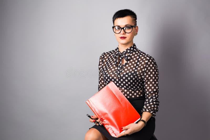 Porträt der glücklichen jungen Geschäftsfrau auf grauem Hintergrund stockfoto