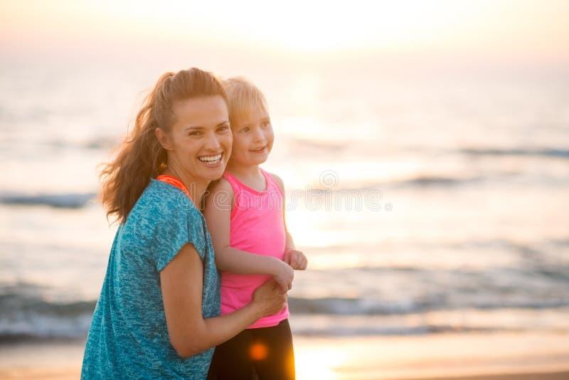 Porträt der glücklichen jungen Mutter und der Tochter auf Strand bei Sonnenuntergang stockbilder