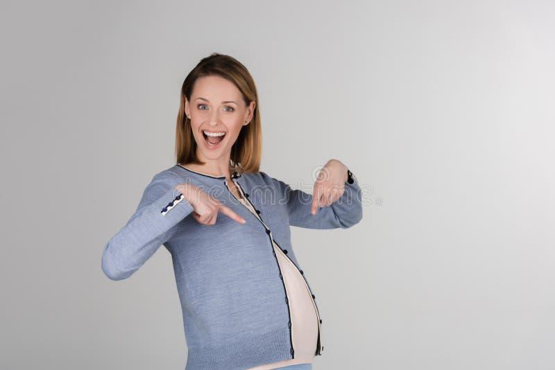 Porträt der glücklichen jungen schwangeren Frau, die im Studio aufwirft lizenzfreie stockbilder