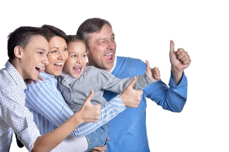 Porträt der glücklichen lächelnden Familie, die sich Daumen zeigt stockfotografie