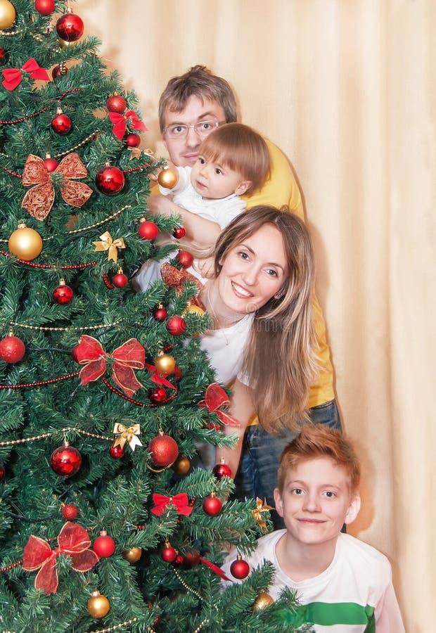 Porträt der glücklichen lächelnden Familie durch Weihnachtsbaum lizenzfreie stockfotos