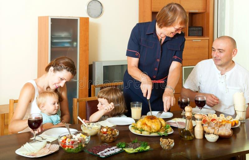 Porträt der glücklichen lächelnden Familie stehen über Feiertagstabelle in Verbindung lizenzfreie stockfotografie