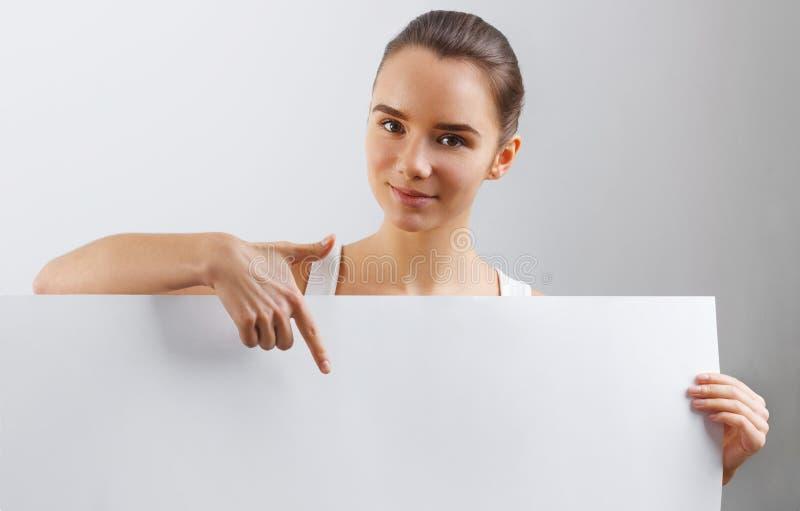 Porträt der glücklichen lächelnden jungen Frau, leeres leeres Schild mit copyspace zeigend Geschäftsfrau, die eine große weiße Fa stockfotos