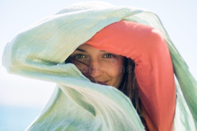 Porträt der glücklichen lächelnden jungen Frau mit dem langen Haar Sie versteckt und stellt einen Schatten mit Schal her stockfotografie