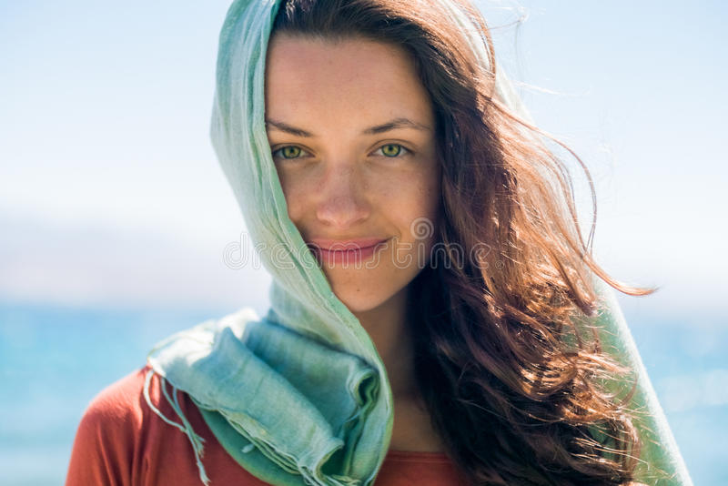 Porträt der glücklichen lächelnden jungen Frau mit dem langen Haar und grünem Schal auf dem Strand- und Seehintergrund lizenzfreie stockbilder