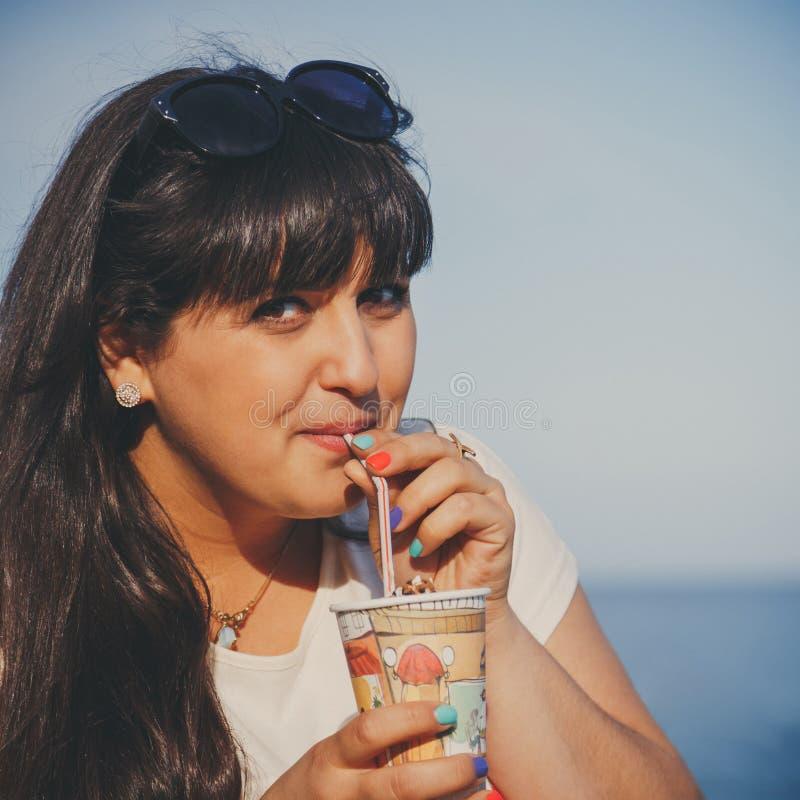 Porträt der glücklichen lächelnden schönen überladenen jungen Frau im weißen T-Shirt süßen Kaffee durch ein Stroh draußen trinken stockfotografie