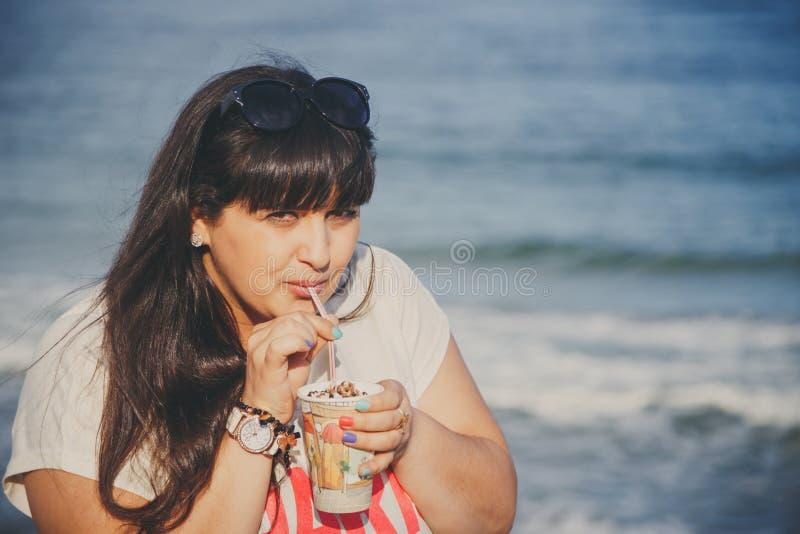 Porträt der glücklichen lächelnden schönen überladenen jungen Frau im weißen T-Shirt süßen Kaffee durch Stroh am Strand draußen t stockfoto