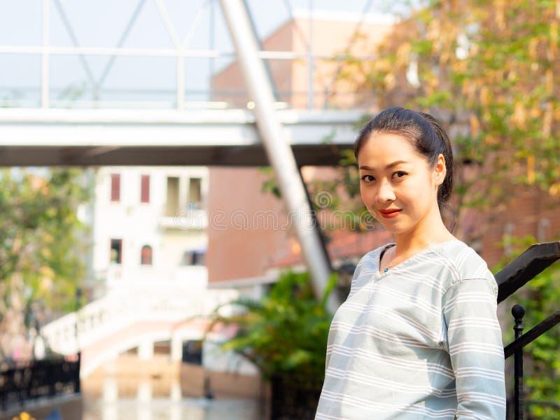 Porträt der glücklichen Lächelnfrau steht auf Tageslicht im Freien stockfotografie