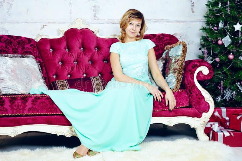 Porträt der glücklichen mittleren erwachsenen Frau, die auf luxuriösem Sofa sitzt stockbild