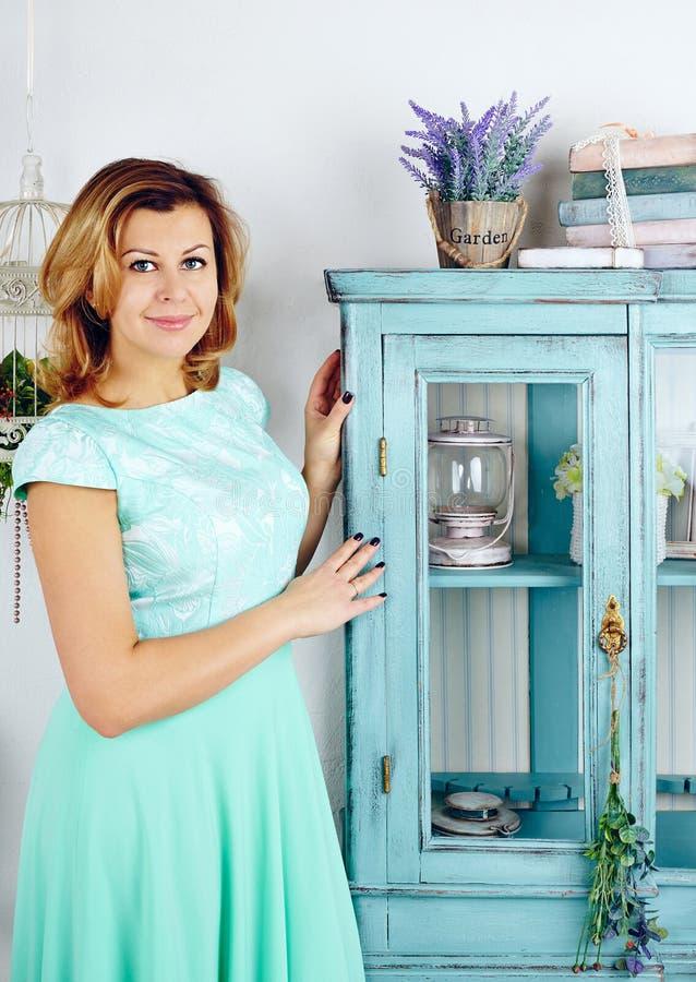 Porträt der glücklichen mittleren erwachsenen Frau, die blaues Kleid trägt lizenzfreie stockbilder