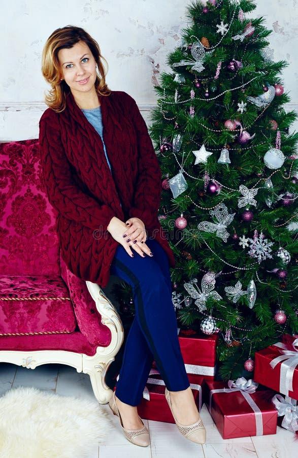 Porträt der glücklichen mittleren erwachsenen Frau, die am Weihnachtsbaum sitzt lizenzfreie stockfotos