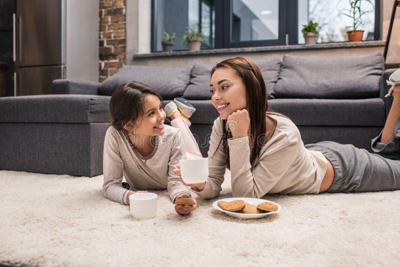 Porträt der glücklichen Mutter und der Tochter, die einander beim Trinken des Tees und Essen von Plätzchen betrachtet stockfotos