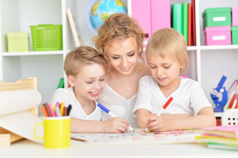 Porträt der glücklichen Mutterzeichnung mit drei Söhnen lizenzfreies stockfoto