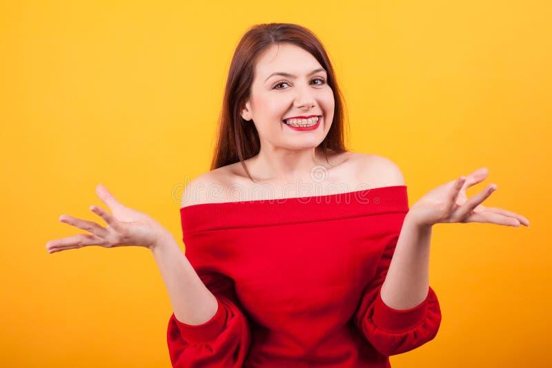 Porträt der glücklichen netten Frau, die mit Klammern auf ihren Zähnen über gelbem Hintergrund lächelt stockfoto