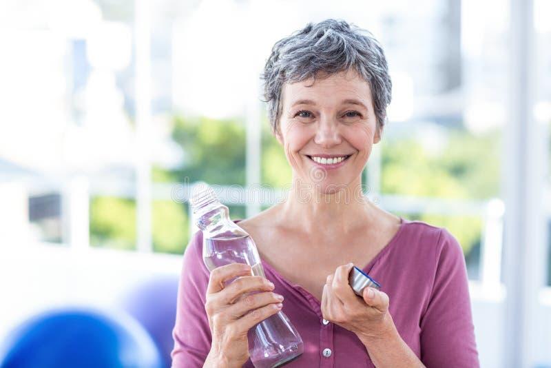 Porträt der glücklichen reifen Frau mit Wasserflasche lizenzfreie stockfotografie